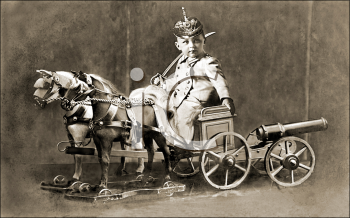 Royalty Free Photo of a German Child and a Vintage Toy Cannon and Horses