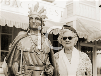 Royalty Free Photo Image of a Woman Standing Beside a Wooden Indian