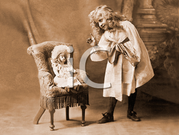 Royalty Free Photo of a Little Girl Talking to Her Doll