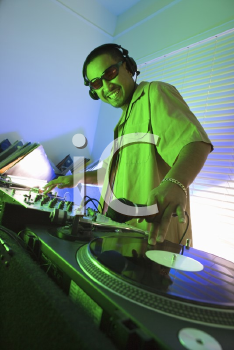 Royalty Free Photo of a Male DJ With Hand on Control Panels of Mixing Equipment