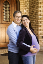 Royalty Free Photo of a Pregnant Woman and Husband Standing in a Doorway