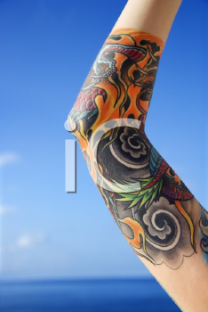 Royalty Free Photo of a Tattooed Woman's Arm With the Pacific Ocean in Background in Maui, Hawaii, USA