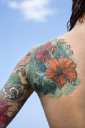 Royalty Free Photo of a Close-up of a Woman's Back and Shoulder Covered With Floral Tattoos