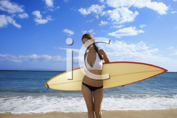 Royalty Free Photo of a Woman in a Bikini Standing With a Surfboard at a Beach in Maui Hawaii