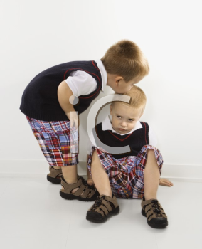 Royalty Free Photo of a Twin Boy Kissing His Brother on the Head