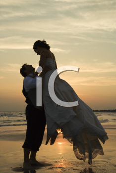 Royalty Free Photo of a Groom Lifting Up a Bride on a Beach at Sunset