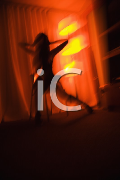 Royalty Free Photo of a Blurred Woman Silhouetted by a Floor Lamp