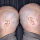 Royalty Free Photo of Identical Twin Bald Men Standing Back to Back