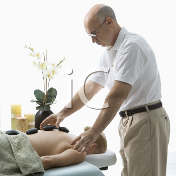 Royalty Free Photo of a Male Massage Therapist Placing Hot Stones on a Woman' Back