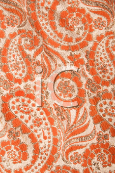 Royalty Free Photo of a Close-Up of Orange Textural Vintage Fabric With Paisley and Metallic Thread Stitching