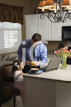 Caucasian father in suit using laptop computer with daughter eating breakfast in kitchen.