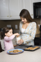 Royalty Free Photo of a Mother Holding a Glass of Milk While Her Daughter Dunks a Cookie