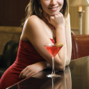 Royalty Free Photo of a Woman in a Red Dress Smiling and Standing at a Bar With a Drink