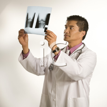 Royalty Free Photo of an Asian American Doctor Examining X-Rays