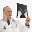 Royalty Free Photo of a Male Physician Holding Up Hand X-Rays Looking Perplexed