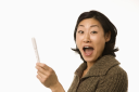 Royalty Free Photo of a Woman Holding Up a Pregnancy Test Looking Excited
