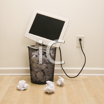 Royalty Free Photo of a Computer Monitor in a Trash Can Surrounded by Crumpled Up Paper