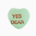 Green candy heart that reads yes dear against white background.