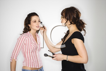 Royalty Free Photo of a Makeup Artist Putting Makeup on a Young Woman