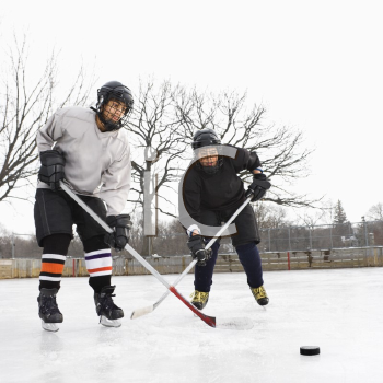 Royalty Free Photo of Two Boys in Ice Hockey Uniforms Playing Hockey on the Ice Rink