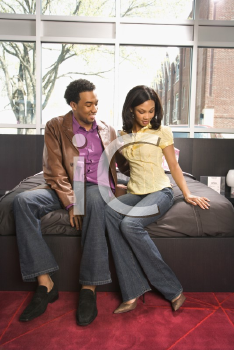 Royalty Free Photo of a Couple Sitting on a bed in a Retail Store