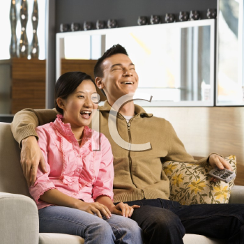 Royalty Free Photo of a Couple Laughing While Watching Television