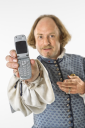 Royalty Free Photo of William Shakespeare in Period Clothing Holding Out a Cellphone