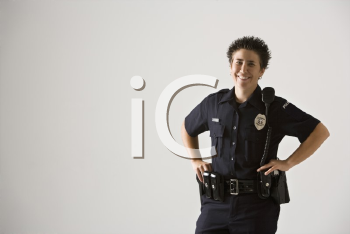 Royalty Free Photo of a Policewoman Standing with Hands on Gun Holster