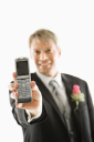 Royalty Free Photo of a Groom Holding Out His Cellphone