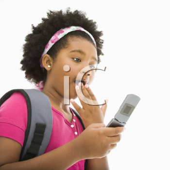 Royalty Free Photo of a Girl With Backpack Reading a Text Message From a Cellphone