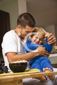 Royalty Free Photo of a Father Tickling His Toddler Son in the Kitchen