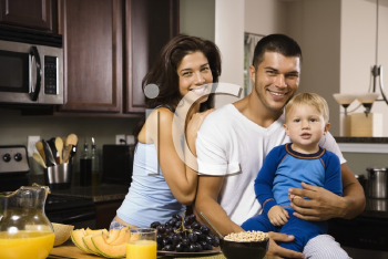 Royalty Free Photo of a Family in a Kitchen at Breakfast Smiling