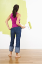 Royalty Free Photo of a Woman Standing Holding a Paint Roller