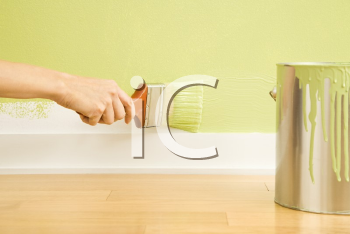 Royalty Free Photo of a Woman's Hand Painting the Trim on a Wall Beside a Paint Can