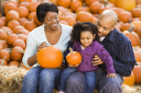 Royalty Free Photo of a Family Sitting on Hay Bales and Holding Pumpkins at an Outdoor Market