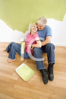 Royalty Free Photo of a Couple Sitting in Front of a Half-Painted Wall with Paint Supplies Snuggling
