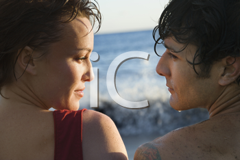 Cropped close-up of young man and woman, wet from swimming, looking at each other, with the ocean in the background. Horizontal shot.