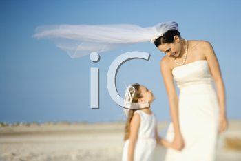 Bride and a flower girl look at each other on a sandy beach. Horizontal shot.