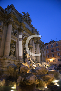 Trevi Fountain at night with lights under the water lighting the statuary. Vertical shot.