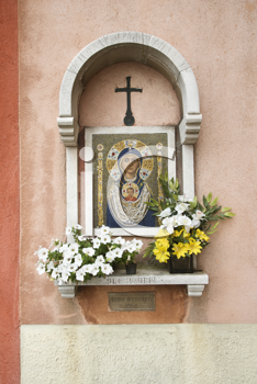 Madonna and Child mosaic at outdoor shrine. Flowers have been left at the shrine. Vertical shot.