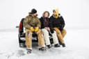 Two young men and a young woman having a beer while sitting on the tailgate of a truck in a winter environment. Horizontal shot.