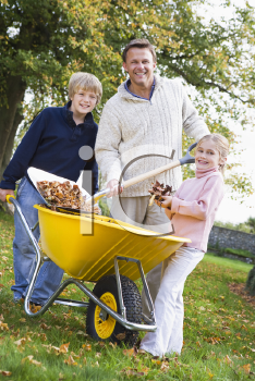 Father and children outdoors shoveling leaves into wheelbarrow and smiling (selective focus)