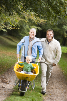Royalty Free Photo of Two Men Pushing a Baby in a Wheelbarrow on a Trail