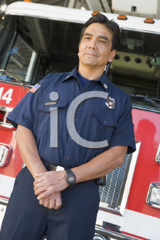 Royalty Free Photo of a Firefighter Standing in Front of an Engine