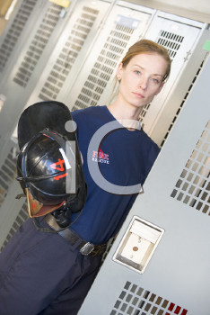 Royalty Free Photo of a Female Firefighter at Her Locker Holding Her Helmet