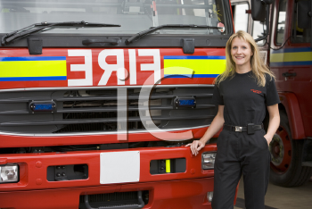 Royalty Free Photo of a Female Firefighter in Front of the Truck