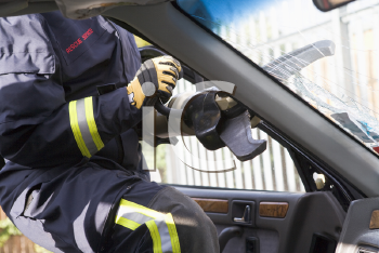 Royalty Free Photo of a Firefighter Cutting Out a Windshield