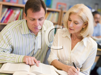 Royalty Free Photo of a Man and Woman Looking Over a Book in a Library