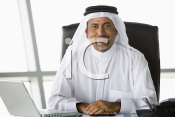 Royalty Free Photo of an Eastern Man at a Desk With a Laptop