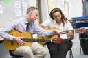 Royalty Free Photo of a Student Taking Guitar Lessons